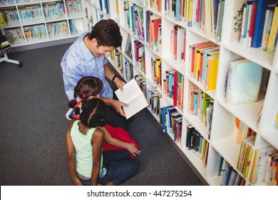 Man reading a book for two kids in a library