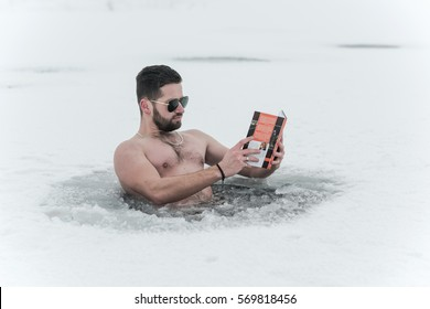 man reading a book in the water ice of the lake