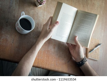 man reading book at wooden table with coffee and notepad. reader and writer creative concept.