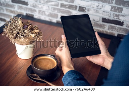 Man reading an e-book on digital tablet device in coffee shop