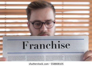Man reading Franchise headlined newspaper