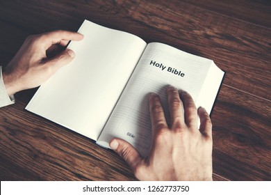 man reading Holy Bible on table