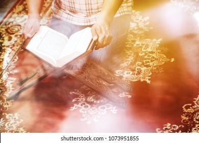 Man reading islamic holy book quran. Daily reading ayat of quran. View through window glass on Muslim man dua reading koran at mosque.