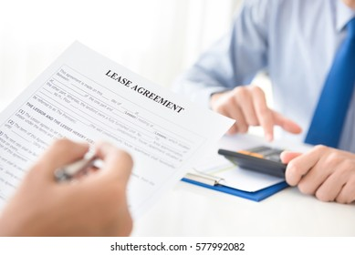 A man reading lease agreement paper, about to fill and sign