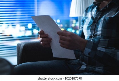 Man reading letter in dark at night. Person writing note in shadows home by the window. Sudden inspiration or bad news. Foreclosure, insurance or mortgage problem.