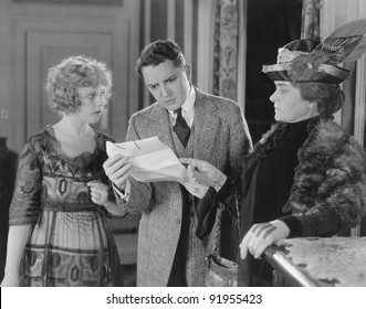 Man reading letter with two women looking over his shoulder