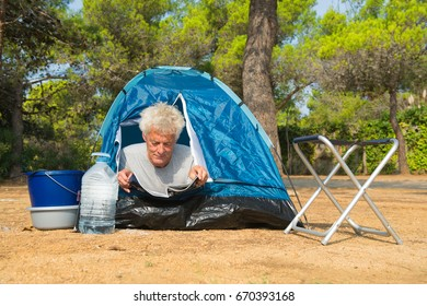 Man reading a magazine at the camping alone with blue dome tent for adventure