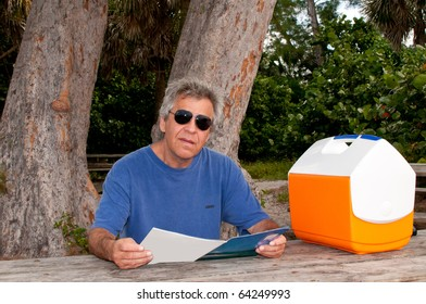 Man reading a magazine at a picnic table