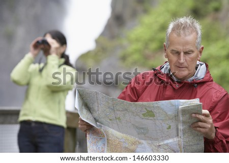 Man reading map with blurred woman looking through binoculars in background