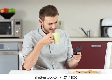 Man reading a message on the mobile phone and holds a cup of coffee at breakfast