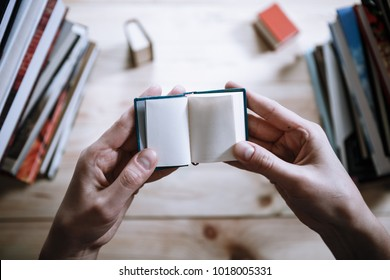 Ein Mann, der unter den großen Büchern in der Bibliothek am Holztisch ein Miniaturbuch liest.