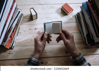 A man reading a miniature book among the big books in the library at the wooden table.