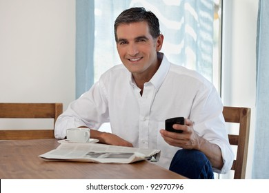 Man Reading Morning Newspaper and Checking Phone