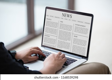 Man reading news article on the laptop / computer screen at office