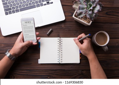 Man reading news article on smartphone and write something on notebook with wooden desk background