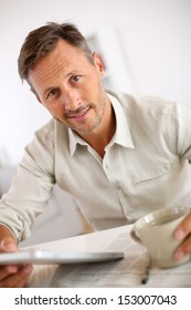 Man reading news on tablet and drinking coffee