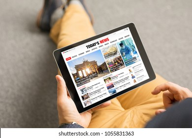 Man reading news website on tablet. All contents are made up.