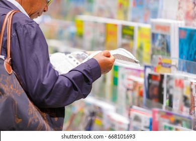 man reading newspaper at bookstand