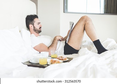 A man is reading a newspaper lying on the bed while is waiting for his wife to have breakfast together. On the bad there is a try with coffees, juices and croissants.