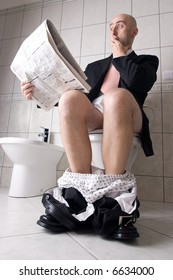 Man reading newspaper on toilet, expressing surprise