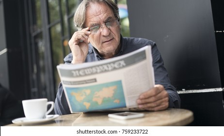 Man reading newspaper in outdoors