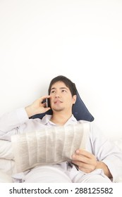 Man reading the newspaper and talking by phone