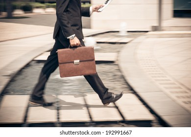 Man reading newspaper while hurrying to work