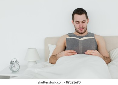 Man reading a novel in his bedroom