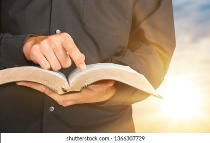 Man reading old heavy book on background