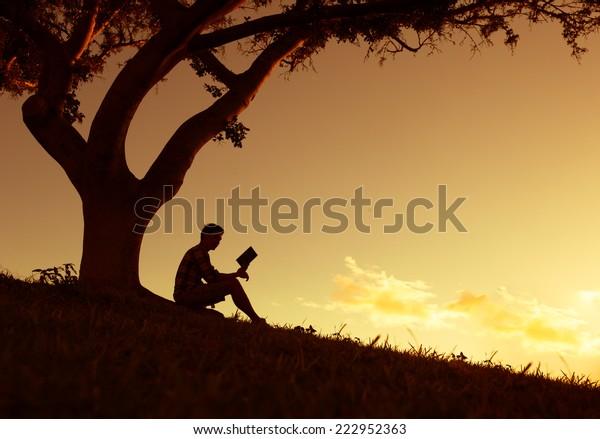 Mann, der im Park liest