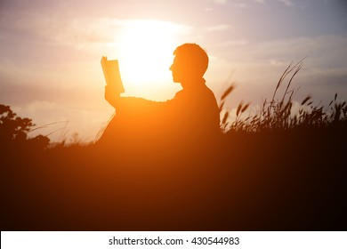 Man reading in the park against sunset. Silhouette of man reading book at sky sunset . warm tone and soft focus