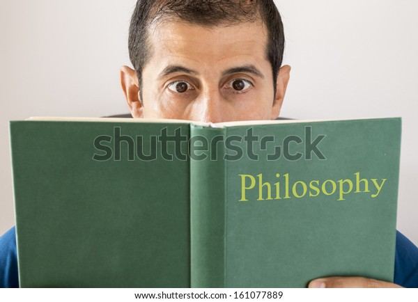 man reading philosophy makes an expression as he stumbles across something difficult