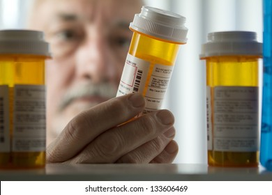 Man reading prescription bottle