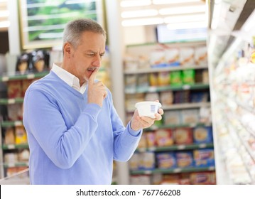 Man reading a product tag in a grocery store