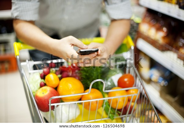 Man reading a text message during shopping