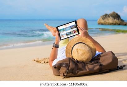 Man reading travel blog on beach
