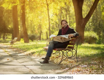 Man reading weekly newpaper in the park. Middle-aged man in long black coat sitting on the bench and enjoying autumn weather.