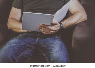 Man reading a white book at home.