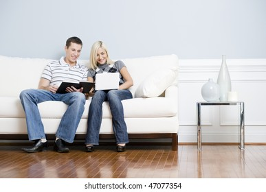 Man is reading, and woman is using a laptop, as they sit side by side on a white couch. Horizontal format.