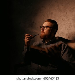 Man reads a book in a dark room and smoking pipe.