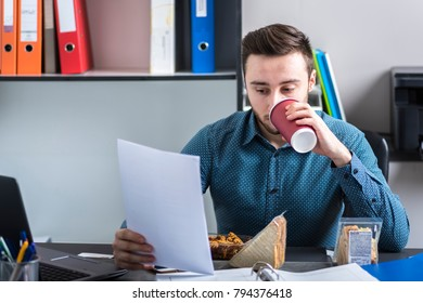 The man reads documents and drinks coffee during a meal break