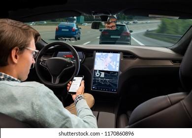 Ein Mann liest Nachrichten online auf einem Smartphone, während sein Auto von einem Autopilot angetrieben wird. Selbstfahrerkonzept