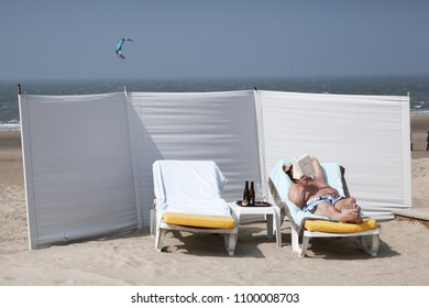 A man reads a newspaper on the beach on a very warm day in Knokke-Heist, Belgium on 20 May, 2018