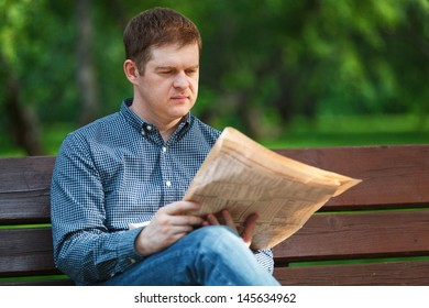 Man reads a newspaper on a bench in the park