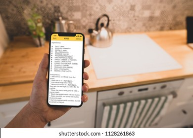 A man reads recipe on a smartphone against of kitchen background