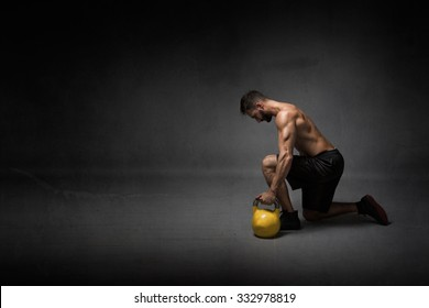 man ready to lifting a kettleball, dark background