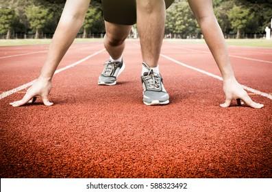 man ready on starter point to run on racetrack