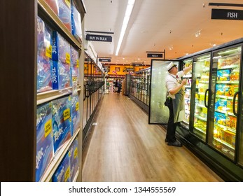 man rearranging food stock in a refrigerator with shoppers in Perris California Stater Brothers.Feb 27,2019