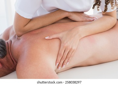Man receiving back massage in spa centre