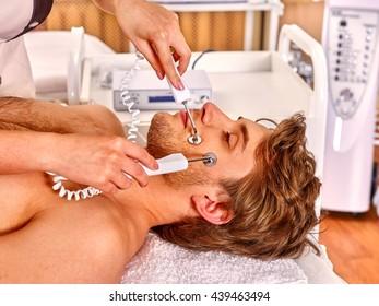 Man receiving electric galvanic facial spa massage at beauty salon. Man facial massage care.